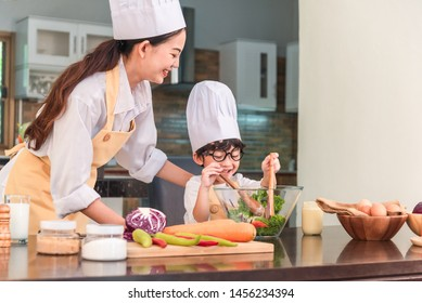 Photo of a smiling asian mother and daughter baking in the kitchen and having fun.