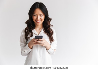 Photo of smiling asian woman with long dark hair holding and using black mobile phone isolated over white background in studio
