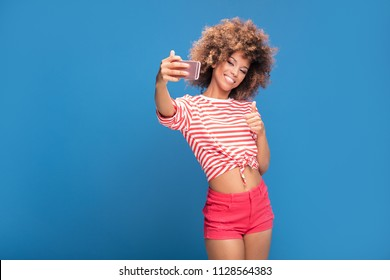 Photo of a smiling beautiful african woman with afro hairstyle, holding mobile phone and taking selfie, standing over blue background.