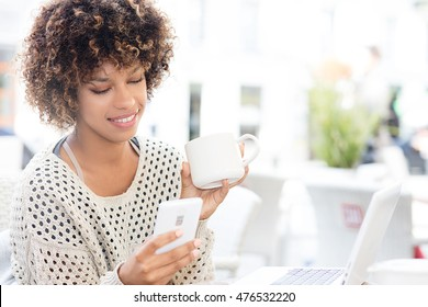 Photo of smiling beautiful woman using mobile phone while sitting at cafe. Young african american woman sitting in a coffee shop and working on laptop.