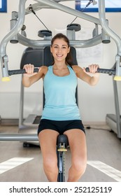 Photo of smiling caucasian brunette training her upper body in gym