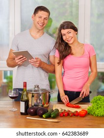 Photo of smiling caucasian couple cooking together at home