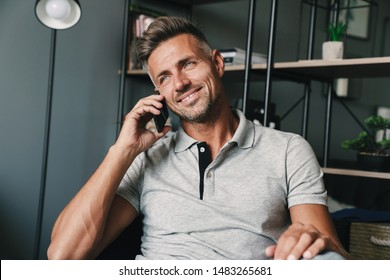 Photo of smiling caucasian man in casual clothing talking on smartphone while sitting on armchair at home