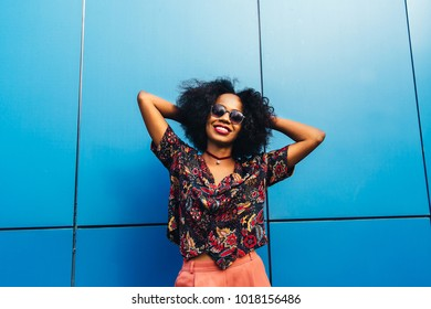 Photo of smiling and charming young african woman in sunglasses, with curly hair, posing on wall background outdoors. Dressed up in stylish blouse.