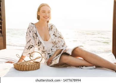 Photo of a smiling cheery young beautiful woman at the beach in a beautiful sunny morning reading magazine.