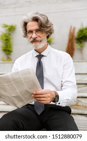Photo of smiling elderly businessman in eyeglasses reading newspaper while sitting outdoors