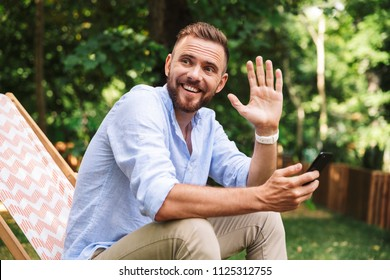 Photo of smiling emotional young bearded man outdoors using mobile phone looking aside waving.