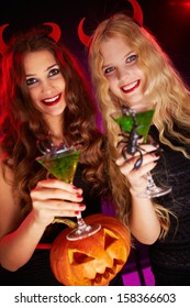 Photo of smiling females holding Halloween pumpkin and cocktails with scorpions