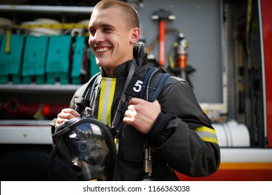 Photo of smiling firefighter standing near fire truck with fire hose