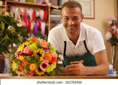 Photo of smiling florist standing next to a colorful bouquet