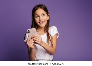 Photo of smiling  girl using mobile phone and looking aside isolated over purple background