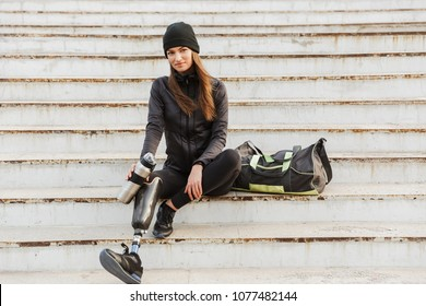 Photo of smiling handicapped woman in sportswear with prosthetic leg sitting at the stairs outdoor and holding thermos cup