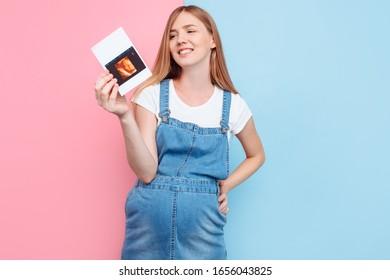 ピンクと青の背景に切り取り線と超音波スキャンを行う、笑顔の幸せな妊婦の写真
