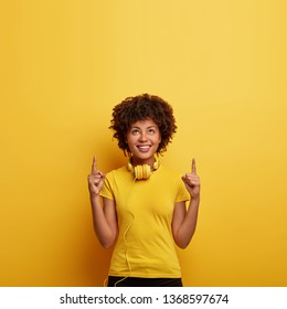Photo of smiling hipster female points above with both index fingers, shows nice place upstairs, listens favourite track in headphones, wears bright yellow t shirt in one tone with background