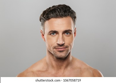 Photo of smiling mature man standing isolated over grey wall background naked. Looking camera.
