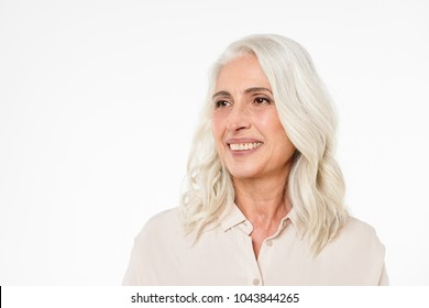 Photo of smiling mature old woman standing isolated over white background wall looking aside.