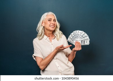 Photo of smiling mature old woman isolated over dark blue background. Looking camera showing money holding in hands.