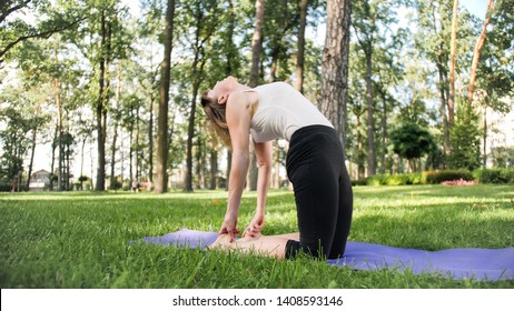 Photo of smiling middle aged woman in fitness clothes doing stretching and yoga exercises. WOman meditating and doings sports on fitness mat on grass at park