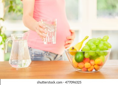 Photo of smiling pregnant woman holding a glass of water