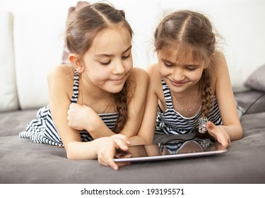 Photo of smiling schoolgirls lying on couch and playing on tablet