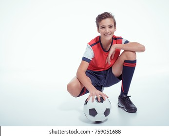 Photo of smiling teen boy in sportswear holding soccer ball - posing at studio