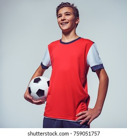 Photo of smiling teen boy in sportswear holding soccer ball - posing at studio, low angle view