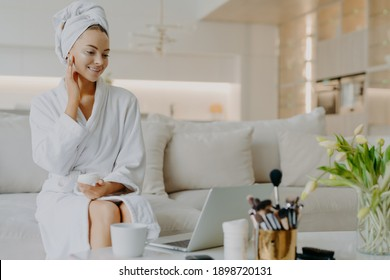 Photo of smiling woman applies nourishing cream on face looks in laptop screen gives advice of skin care dressed in bathrobe and towel sits at comfortable sofa has rejuvenation procedure. Cosmetology