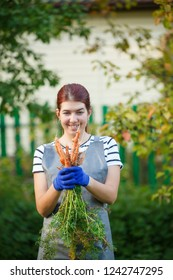 Photo of smiling woman with carrot in hands on garden