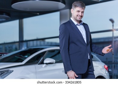Photo of smiling young businessman buying new car