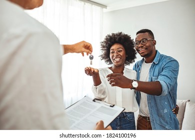 Photo of a smiling young couple thanking to the agent for the new house. Homeowners receiving their new house keys. Close up of a happy homeowners receiving their new house keys from a estate agent