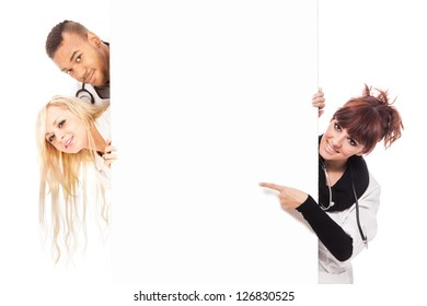 Photo of smiling young doctors in front of a white message board