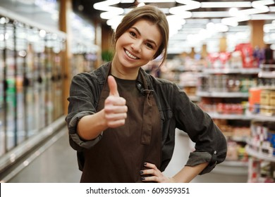 Photo of smiling young lady in supermarket standing and posing. Looking at camera and showing thumbs up.
