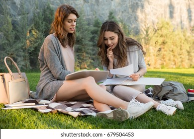 Photo of smiling young two women sitting outdoors in park writing notes. Looking aside.