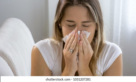Photo of sneezing woman in paper tissue