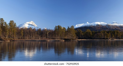 Photo of snow-covered mountain tops reflecting on lake ice in Norway.