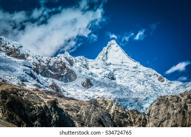 Photo of snowy Alpamayo, one of most conspicuous peaks in Cordillera Blanca of Peruvian Andes in Parque Nacional Huascaran in South America.