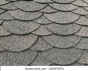 Photo of soft shingles tiles closeup. The texture of the soft roof. Roofing, made of shingles. Texture of shingles. Background on the topic of roofing construction materials.