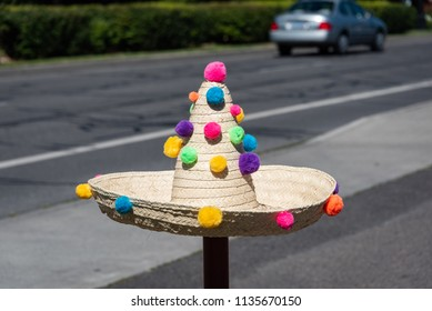 Photo of a sombrero on a post with colorful pom poms.