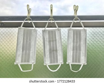 Photo of some white reusable face masks are hanging on a cloth rack while drying after washing. coronavirus protection concept
