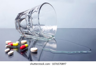 Photo of a spilled water glass with pills laying on vitreous table.