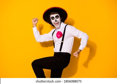 Photo of spooky monster guy raise hands fists open mouth excited undead toreador win fight mad bull wear white shirt death costume sugar skull suspenders isolated yellow color background