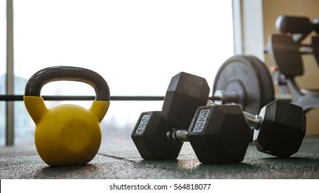 Photo of sport equipment in gym. Dumbbells on floor.