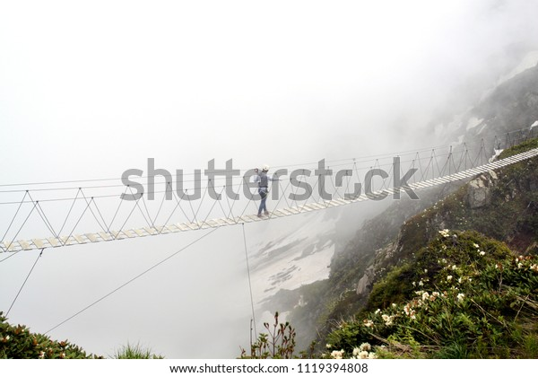 Photo of a sport man walking on a cable car over an abyss in the mountains