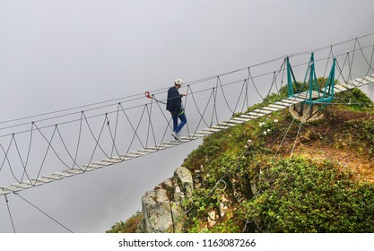 Photo of a sport man walking over an abyss in the mountains