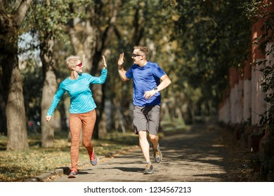 Photo of sporting man and woman doing handshake on morning jog