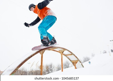 Photo of sportive man skiing on snowboard with springboard