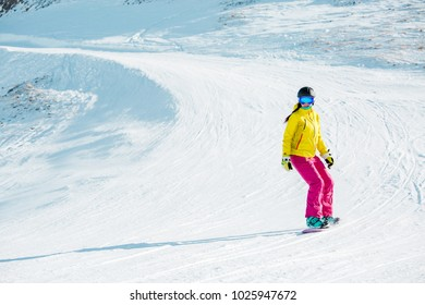 Photo of sports girl in helmet riding snowboard from mountain slope