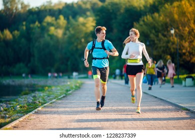 Photo of sports men and women running in park