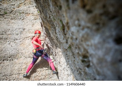 Photo of sports woman in red hard hat with carbine in hand climbing mountain