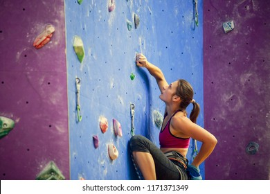 Photo of sports woman with talc bag behind back practicing on climbing wall